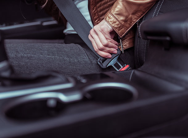 Close Up, A Female Hand Fastens A Seat Belt In A Car, Background Leather Jacket In The Summer In Spring And Autumn, Traffic Safety In The Car.